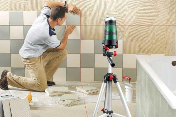 Мастер укладывает плитку при помощи лазерной разметки